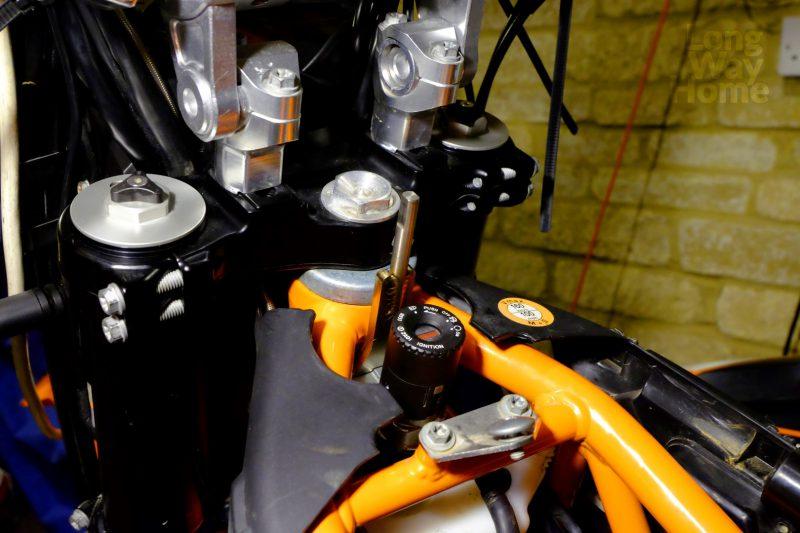 Z zamontowanym bolcem prowadzącym ramię amortyzatora - With steering damper pin assembly installed